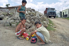 With toy trucks playing latino boys and real truck. Brazil, Pernambuco, village Gravata: boys play lorry driver along the side of the road. On the dirt road stock image