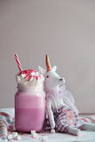 Toy unicorn with pink milk shake with cream, marshmallow and colorful decoration. Milk shake, cocktail. Unicorn coffee. Stock Images