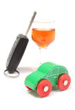 Toy vehicle, car key and glass of wine. White background Royalty Free Stock Images