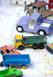 Toy vehicles on a road map. Toy cars travel across a folded road map Stock Photography