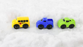 Toy Vehicles through a Snowy Pass. High view of three toy vehicles traveling along a pass through deep snow Stock Photo