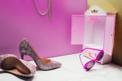 Toy wardrobe with real size high heels and vintage sunglasses in miniature. Pink room stock photos