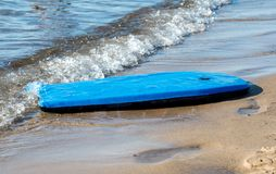 Toy washed up on the beach. A bright blue beach board washes up on the shore at a beach on Lake Michigan stock photography