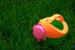 Toy watering-can on the grass Royalty Free Stock Photography