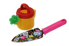 Toy watering can and a shovel. Royalty Free Stock Photo
