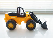 Toy Wheel Loader Close up. Toy Industrial Vehicle, Plastic Wheel Loader Excavator for Earth Moving Works at Construction Site, Miniature Earth Mover, Backhoe Stock Photography