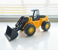 Toy Wheel Loader Close up. Toy Industrial Vehicle, Plastic Wheel Loader Excavator for Earth Moving Works at Construction Site, Miniature Earth Mover, Backhoe Royalty Free Stock Images