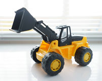 Toy Wheel Loader Close up. Toy Industrial Vehicle, Plastic Wheel Loader Excavator for Earth Moving Works at Construction Site, Miniature Earth Mover, Backhoe Royalty Free Stock Photos