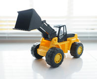 Toy Wheel Loader Close up. Toy Industrial Vehicle, Plastic Wheel Loader Excavator for Earth Moving Works at Construction Site, Miniature Earth Mover, Backhoe Royalty Free Stock Photography