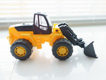 Toy Wheel Loader Close up. Toy Industrial Vehicle, Plastic Wheel Loader Excavator for Earth Moving Works at Construction Site, Miniature Earth Mover, Backhoe Stock Images