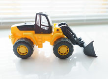 Toy Wheel Loader Close up. Toy Industrial Vehicle, Plastic Wheel Loader Excavator for Earth Moving Works at Construction Site, Miniature Earth Mover, Backhoe Royalty Free Stock Photo