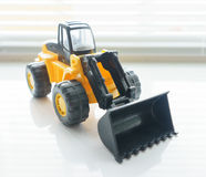 Toy Wheel Loader Close up. Toy Industrial Vehicle, Plastic Wheel Loader Excavator for Earth Moving Works at Construction Site, Miniature Earth Mover, Backhoe Stock Photo