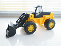 Toy Wheel Loader Close up. Toy Industrial Vehicle, Plastic Wheel Loader Excavator for Earth Moving Works at Construction Site, Miniature Earth Mover, Backhoe Stock Photos