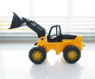 Toy Wheel Loader Close up. Toy Industrial Vehicle, Plastic Wheel Loader Excavator for Earth Moving Works at Construction Site, Miniature Earth Mover, Backhoe Stock Image