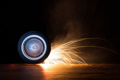 Toy wheel spinning on black background with sparks flying Stock Image
