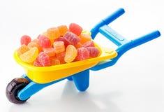 Toy wheelbarrow full of jellies Royalty Free Stock Photos