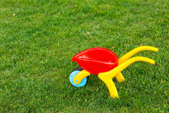 Toy wheelbarrow on the green grass Royalty Free Stock Photography
