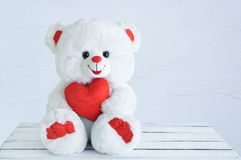 Toy white bear with a heart in his hands. Sits on a wooden table stock photos