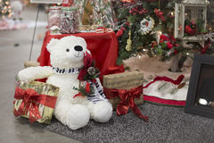 Toy White Polar Bear Sitting underneath a Christmas Tree full of. Gifts under neight Christmas Tree with Polar Teddy Bear royalty free stock photos