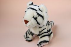 Toy white tiger cub on peach background with reflection of shadow. Soft toy white tiger cub on peach background with reflection of shadow stock photography