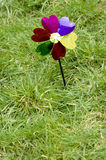 Toy windmill flower on green grass background,concept of green energy. Stock Images