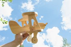 Toy airplane in hand and blue cloudy sky as background. Royalty Free Stock Photography