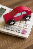 Toy Wooden Car On Calculator rojo para ilustrar el coste de viajar en automóvili imagen de archivo