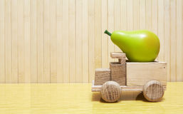 Toy wooden car with green pear Royalty Free Stock Photography