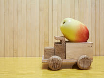 Toy wooden car with yellow apple Royalty Free Stock Photo