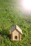 Toy wooden house on the bright grass. Sun glare on the right side. Copy space. Real estate concept. royalty free stock photography