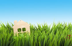 Toy wooden house in green grass over blue sky Royalty Free Stock Images