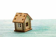 Toy wooden model house as symbol family and love concept on sunny. Old blue wooden background buying a house, mortgage, repair, stability stock photo