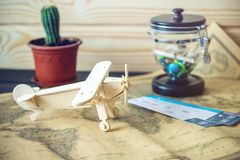 Toy wooden plane on a world map with colored stones and shells from the sea in a retro style. Concept of travel, discovery and exploration of new stock photo