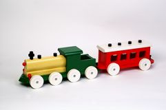 Toy Wooden Train. Old yellow and green wooden toy locomotive with red coach on white background Royalty Free Stock Photo