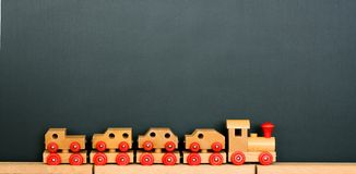 Toy Wooden Trains in Front of Blackboard Background Stock Photo