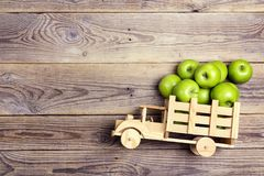 Toy wooden truck with green apples in the back on wooden backgr