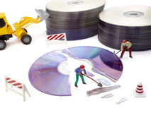 Toy workers repairing computer. Miniature toy workers repairing broken compact disk Royalty Free Stock Photos