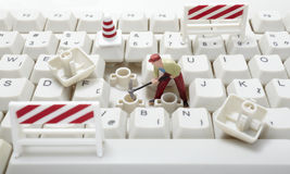 Toy workers repairing computer keyboard Royalty Free Stock Photography