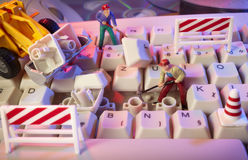 Toy workers repairing computer keyboard Stock Image