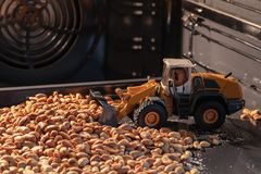 Toy yellow bulldozer collects roasted nuts in the oven. Toy bulldozer collects roasted nuts in the oven stock image