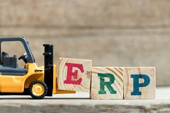 Toy yellow forklift hold letter block E to complete word ERP Abbreviation of Enterprise Resource Planning stock photography