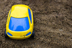 Toy yellow passenger car with blue glass in the sand, Royalty Free Stock Images