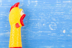 Toy yellow shrilling chicken on blue wooden background Royalty Free Stock Photography