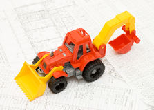 Toy yellow tractor on projects. Close up Stock Photos