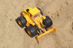 Toy yellow tractor on the sand. Stock Image