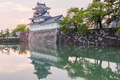Toyama castle with beautiful sunset and reflection in water. Stock Photography