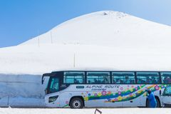 TOYAMA , JAPAN - April 30, 2017:Bus on the road between the snow. TOYAMA , JAPAN - April 30, 2017:People are walking at Tateyama Kurobe Alpine Route with bus on Stock Image