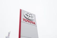 Toyota logo, ställning nära en bilåterförsäljare, Toyota annonsering Royaltyfria Bilder
