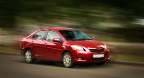 Toyota red car. Toyota red car on a blurred in motion background stock image