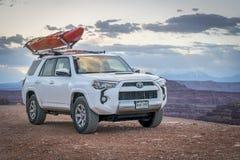 Toyota 4runner SUV con un kajak en el tejado en un rastro del barranco Imagen de archivo